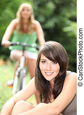 Young woman sitting on the grass with her friend on a bike in the background