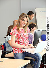 Student with laptop in classroom
