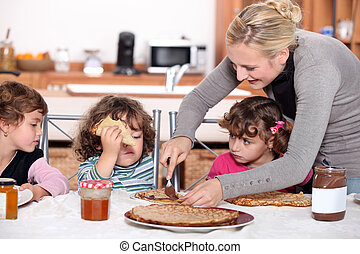 Mother preparing breakfast for kids
