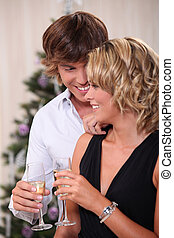 Intimate young couple drinking champagne at Christmas