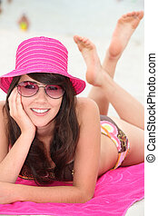 Young woman lying on the beach in bikini and a bright pink...