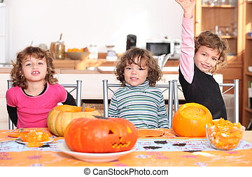 Kids preparing pumpkins for Halloween