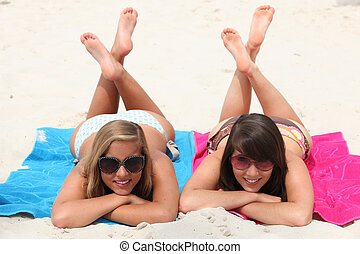 Lazy day on the beach: two girls lying on their stomachs...
