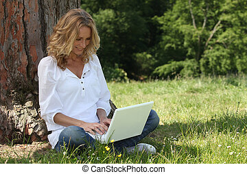 Woman laughing at her laptop computer in the park
