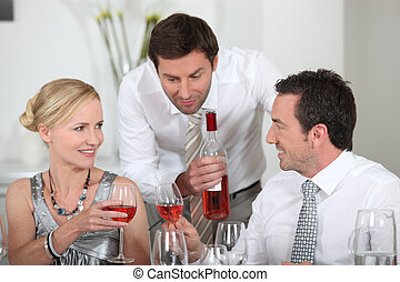 Man serving rose wine at a dinner party