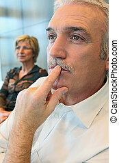 Man watching something thoughtfully