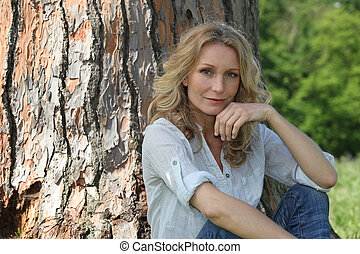 Blond woman sat by tree hand touching face