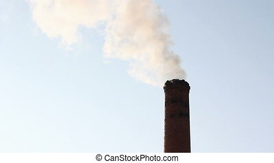 Pollution, smoke and steam from the chimney of an industrial...