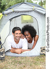 Young couple camping in tent