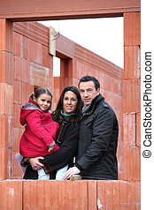 couple and daughter having their house built