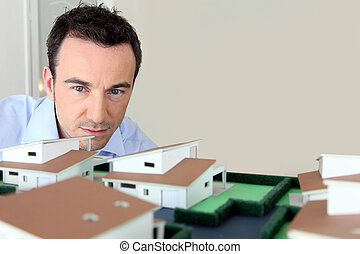Architect looking at model housing