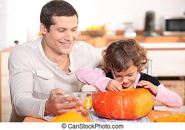 Father carving pumpkins with his daughter