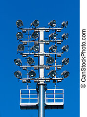 Stadium lighting with a lot of reflectors against blue sky