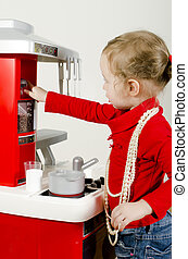 Little cute girl playing in childrens kitchen