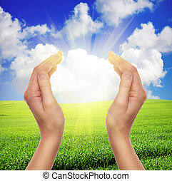 female hands holding sun over green field of grass and blue sky
