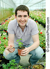 Care - An image of a man with a plant in a pot