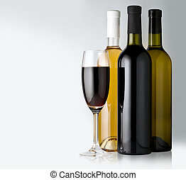 White and red wine bottles with one glasses on the white...