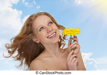 beautiful young woman with flowing hair with a yellow gerbera flower against the sky with clouds and sun