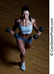 Athletic trainer shows examples of exercises in the gym -...