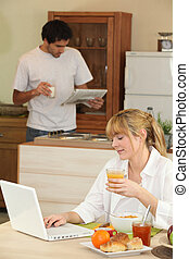 a woman having breakfast, her husband is reading newspaper