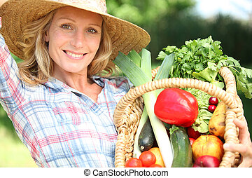 Woman with a straw hat holding basket of vegetables