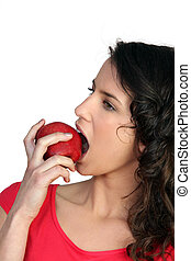 Young brunette biting into apple