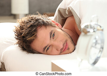 young man in bed waking up