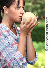 Girl smelling melon