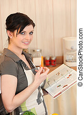 Woman eating a carrot and looking at a cookbook