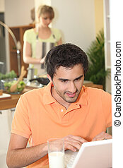 Man looking at his laptop while his wife prepares dinner
