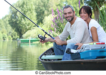 Couple in row boat fishing
