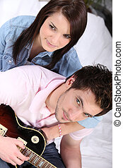 a young couple on bed, the man is playing guitar