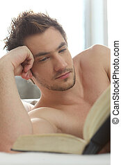 Young man reading a book in bed
