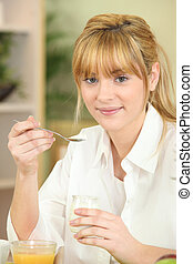 Young woman eating yoghurt at breakfast