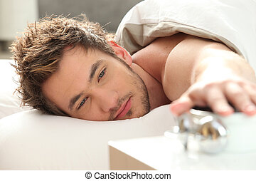 Man turning off alarm clock