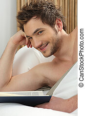 Young man reading in bed