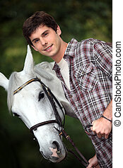Closeup of young man with a white horse