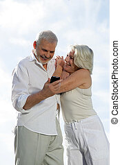 senior couple on vacation taking picture with a cell phone