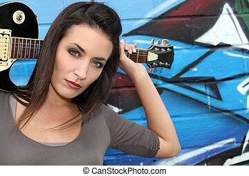 Female guitarist standing in front of a graffiti wall
