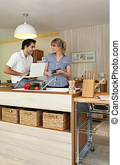 Young man and young woman smiling in kitchen