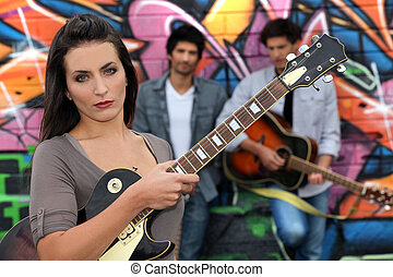 Female guitarist standing with band members in front of a...