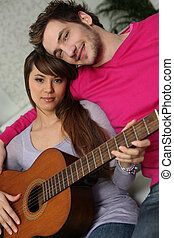 Girl and boy with guitar sitting on a couch