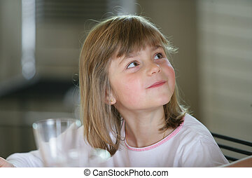 Little girl sat at kitchen table