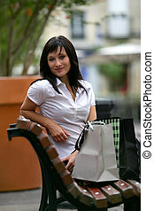 Woman sat on bench after successful shopping trip