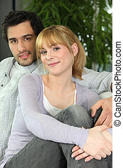 Portrait of young couple sitting in sofa