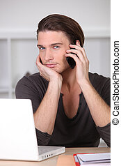 handsome blue-eyed young man phoning and computer