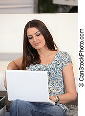 Relaxed woman using a laptop computer in her lounge