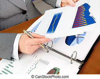 Analyzing investment charts - Businesswoman analyzing...