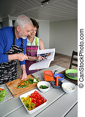Elderly couple preparing a meal with the help of a cookbook