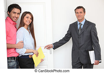 Estate-agent showing couple around property